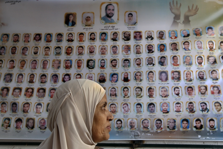 <p>A Palestinian woman looks at a banner bearing names and photos of Palestinian prisoners held in Israeli jails in front of the International Red Cross building in East Jerusalem. Oct. 12, 2011.</p>