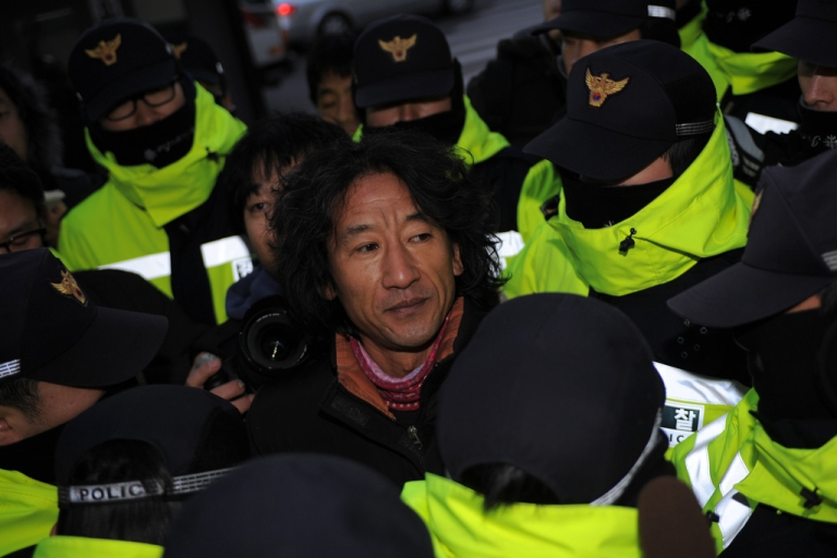 <p>An pro-North Korean activist is surrounded by Seoul policemen before showing his respect to the death of North Korean leader Kim Jong Il on Dec. 26, 2011.</p>