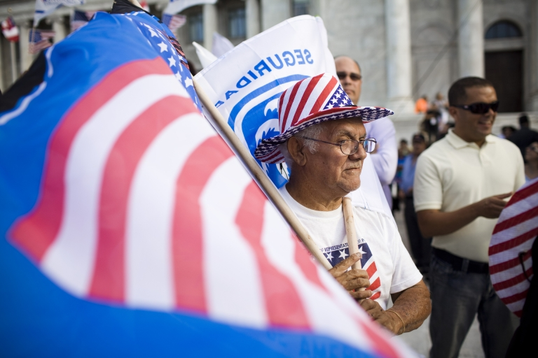 <p>Roberto Maldonado, 75, sells flags at a New Progressive Party rally where Mitt Romney was campaigning Friday on the North Side of the Capitol building in San Juan, Puerto Rico.</p>
