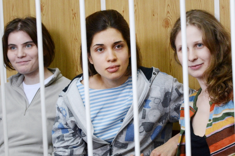 <p>Members of the all-girl punk band Pussy Rio,  Nadezhda Tolokonnikova (C), Maria Alyokhina (R) and Yekaterina Samutsevich (L), sit behind bars during a court hearing in Moscow on July 20, 2012.</p>