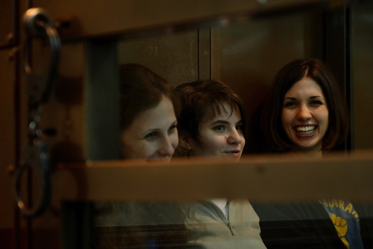 <p>Members of the all-girl punk protest band 'Pussy Riot' (L-R) Yekaterina Samutsevich, Maria Alyokhina and Nadezhda Tolokonnikova, sit in a glass-walled cage in Moscow, on Oct. 1, 2012.</p>