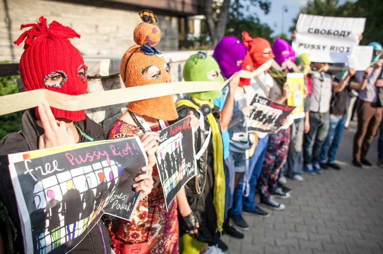 <p>Supporters of the Russian punk band 'Pussy Riot' wear masks and hold placards demanding their freedom as they protest in front of of the Russian embassy in Warsaw on August 17, 2012.</p>