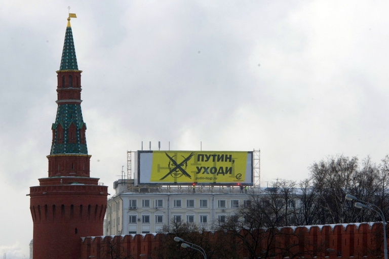 <p>Opposition activists hang their banner reading: 'Putin, leave!' atop a bulding's roof, just over the Moskva River river from the Kremlin (foreground) in Moscow, on February 1, 2012</p>