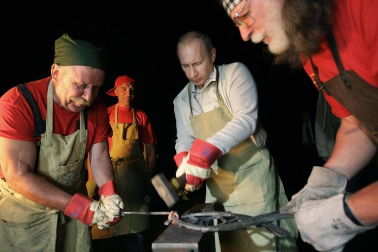 <p>Russia's Prime Minister Vladimir Putin (C) strikes iron as he visits