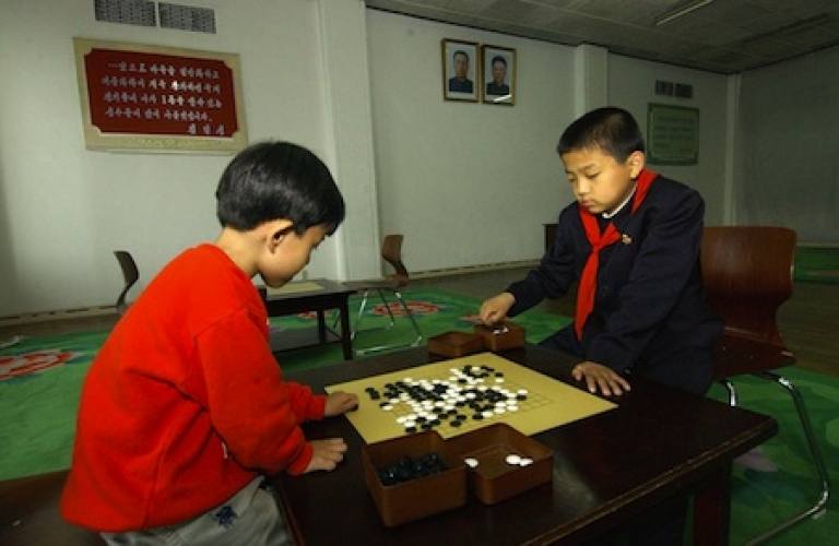 <p>North Korean students play a game of 'go' during their class at the Mangyondae school children's palace in Pyongyang, North Korea, as portraits of North Korean leader Kim Jong-Il (top R) and his late father Kim Il-Sung (top-L) look down from the walls.</p>