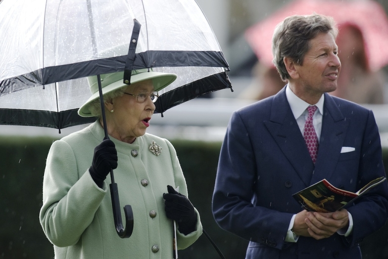 <p>The Queen shelters from the rain with racing manager John Warren at Newbury racecourse on April 21, 2012 in Newbury, England.</p>