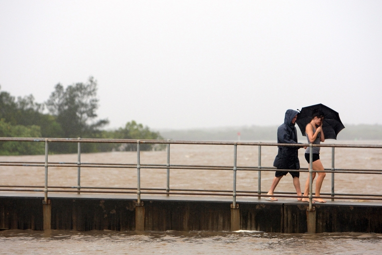 <p>Maroochydore residents walk in torrential rain across the rising Maroochy River on January 11, 2011 on the Sunshine Coast, Australia.</p>