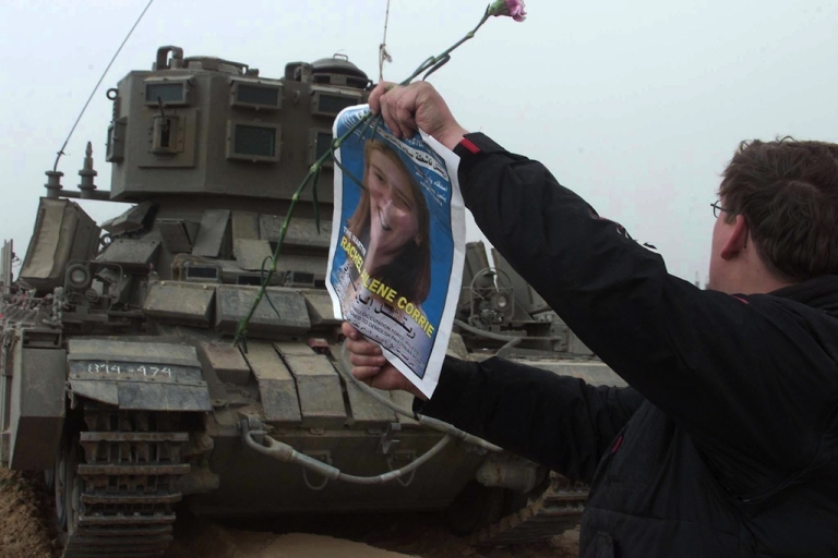 <p>A member of the International Solidarity Movement waves a picture of Rachel Corrie in front of an Israeli tank during a demonstration where Corrie was killed on March 18, 2003. ISM members and Palestinians protested the killing of Corrie who was crushed to death 16 March by an Israeli army bulldozer in Rafah as she and other activists tried to prevent the destruction of Palestinian homes, Palestinian officials and a US witness said.</p>