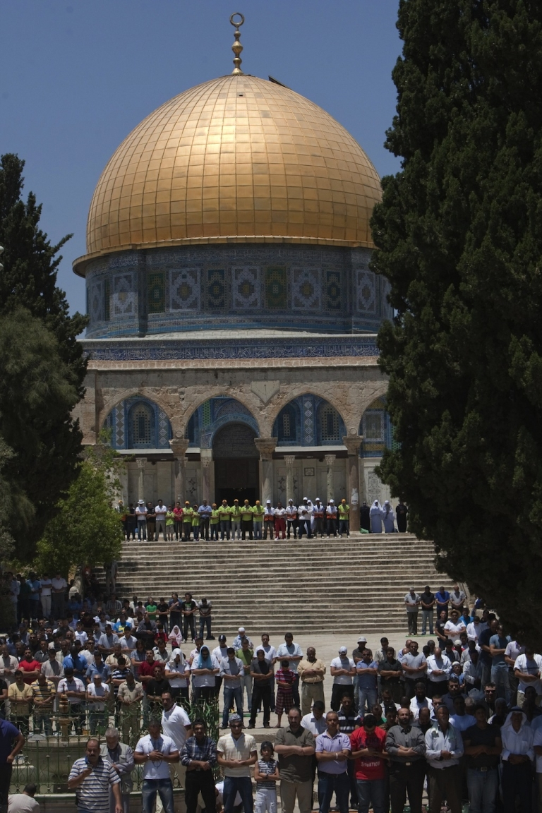 <p>Palestinian worshippers pray outside the Dome of the Rock at the Al-Aqsa Mosque compound in Jerusalem during the first Friday prayers of the Muslim holy month of Ramadan on July 20, 2012.</p>