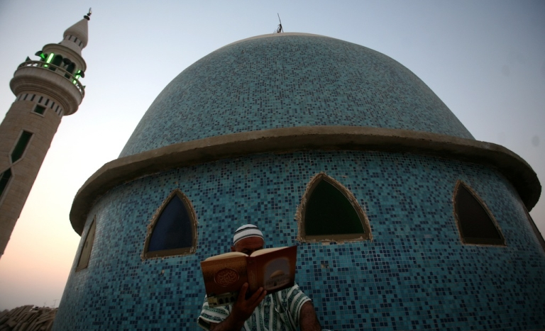 <p>A Palestinian man reads the Quran outside a mosque in the West Bank city of Jenin on the first day of the Muslim holy fasting month of Ramadan on July 20, 2012.</p>