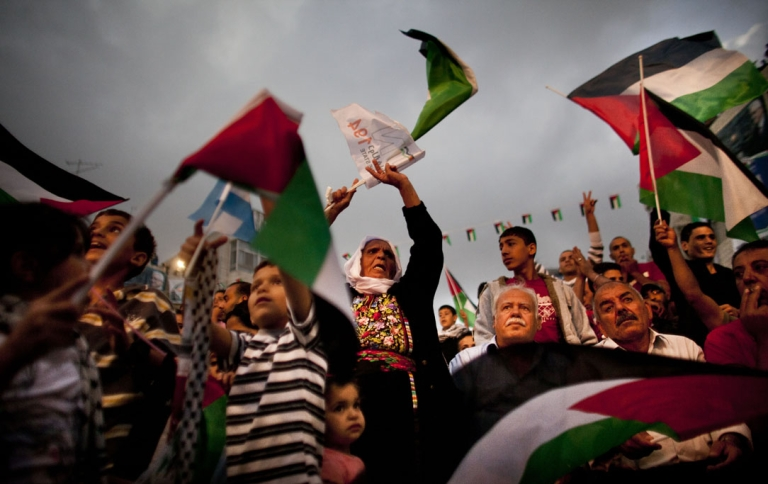 <p>Palestinians in Ramallah watch their President Mahmoud Abbas on TV as he delivers his speech at the United Nations during the General Assembly.</p>