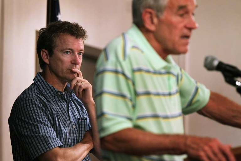 <p>CEDAR RAPIDS, IA - AUGUST 10:  U.S. Senator Rand Paul (L) (R-KY) listens to his father Texas Congressman and Republican presidential hopeful Ron Paul speak at a campaign stop  August 10, 2011 in Cedar Rapids, Iowa.  (Photo by Scott Olson/Getty Images)</p>