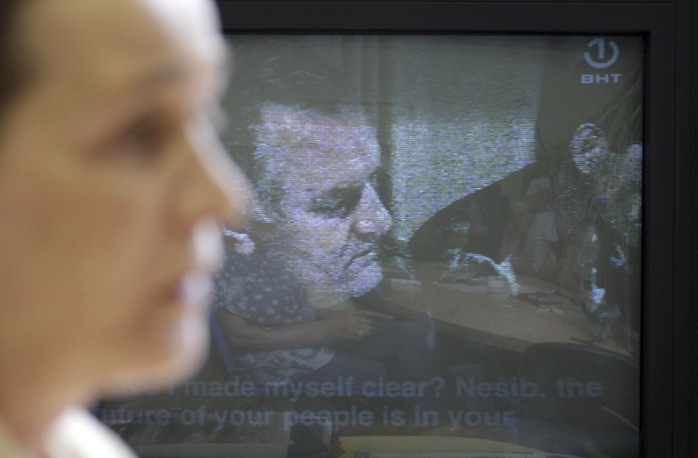 <p>A Bosnian Muslim woman, survivor of the 1995 Srebrenica massacre, Sabaheta Fejzic, watches the news on the arrest of Ratko Mladic (on tv screen) in Sarajevo, on May 26, 2011. Ratko Mladic, who was arrested Thursday after almost 16 years on the run, was the Bosnian Serb army commander whose brutish leadership is blamed for the worst atrocities in Europe since World War II. Mladic, 69 not only ordered and masterminded the Srebrenica massacre of 8,000 Muslim men and boys but also the 44-month siege of Sarajevo which cost an estimated 10,000 lives.</p>