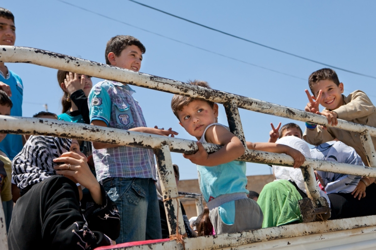 <p>Syrian children ride in the back of a truck as they return to their village of Kfar Sijna on July 10, 2012, the day after it came under fire by Syrian government forces. The Red Cross has officially classified the Syrian conflict as a civil war, in order to hold combatants to international humanitarian law and the Geneva Conventions.</p>