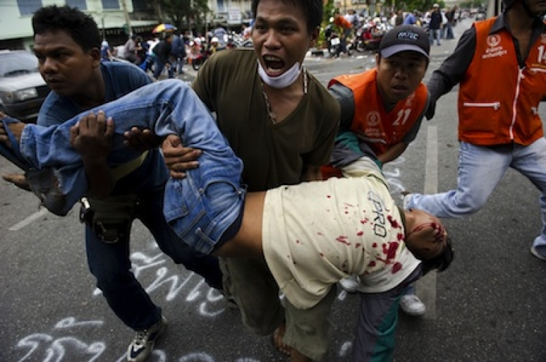 <p>''Red Shirt'' anti-government protesters carry a man who was shot during clashes between demonstrators and security forces in Bangkok on May 15, 2010.</p>