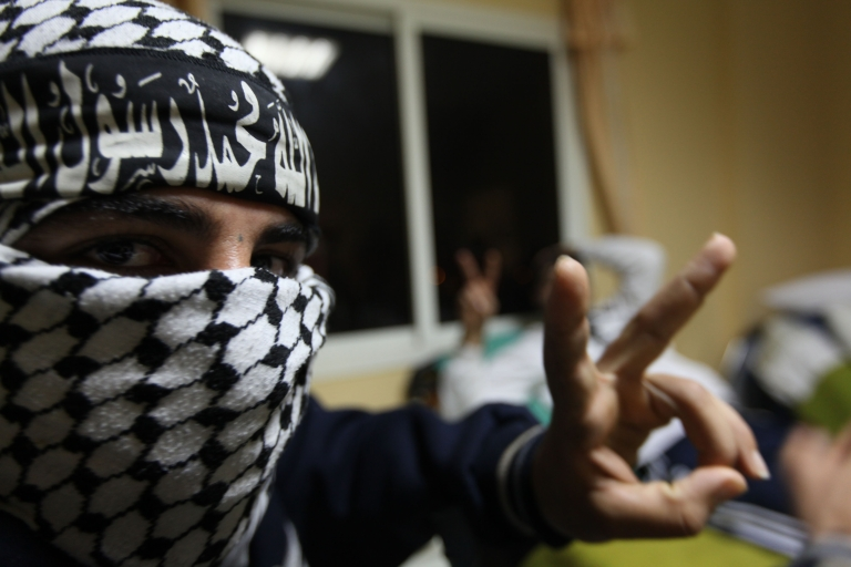 <p>A rebel wearing a chequered keffiyeh and a headband that reads in Arabic: 'There is no God but God, Mohammed is his messenger', flashes the V-sign for victory.</p>
