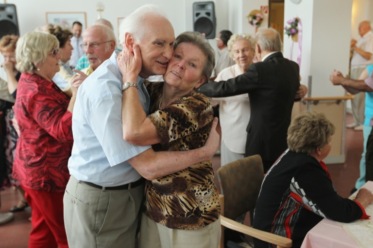 <p>An elderly couple embrace while dancing during an afternoon get-together in the community room of a senior care home in Berlin, Germany.</p>