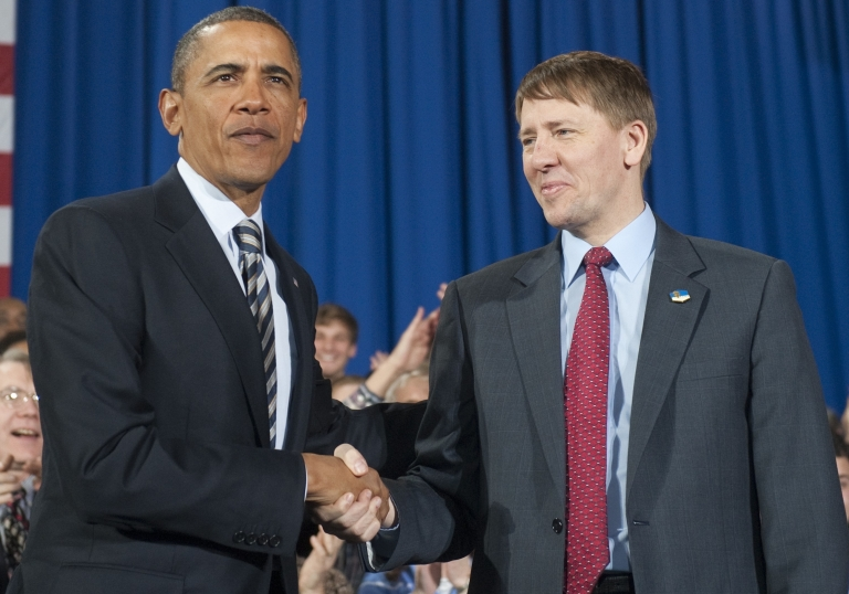 <p>President Barack Obama shakes hands with Richard Cordray (R) before speaking about the economy at Shaker Heights High School in Shaker Heights, Ohio, on Jan. 4, 2012.</p>