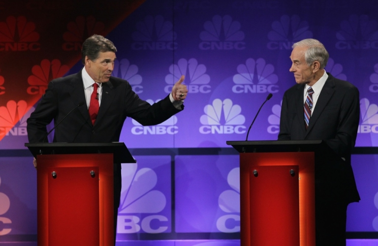 <p>Republican presidential candidate Texas Governor Rick Perry (L) makes a point as U.S. Representative Ron Paul (R-TX), listens at a debate hosted by CNBC and the Michigan Republican Party at Oakland University on November 9, 2011 in Rochester, Michigan.</p>