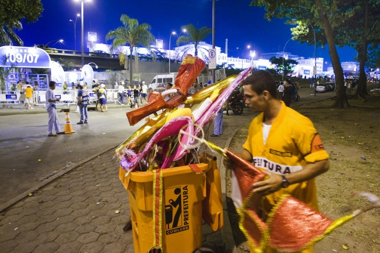 <p>A garbage collector throws away fancy dresses abandoned by revellers after the last street band Carnival parades in downtown Rio de Janeiro on February 25, 2009.</p>