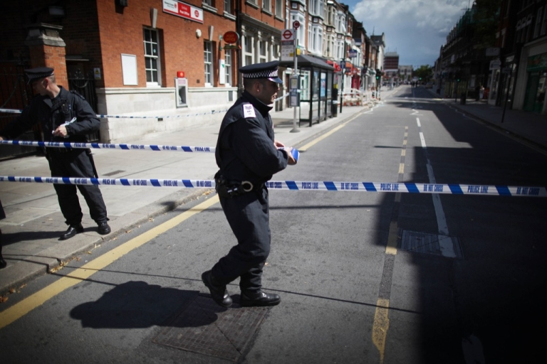 <p>A policeman puts tape across Church Street in Enfield on August 8, 2011 in London, England.</p>
