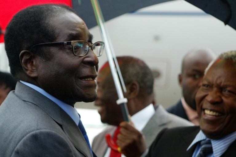 <p>Zimbabwean President Robert Mugabe, 88, chats with State Security Minister Sydney Sekeramayi on April 12, 2012 upon his arrival at the Harare international airport from Singapore following a two-week absence, which sparked reports that he was battling for life in a hospital in the city-state.</p>