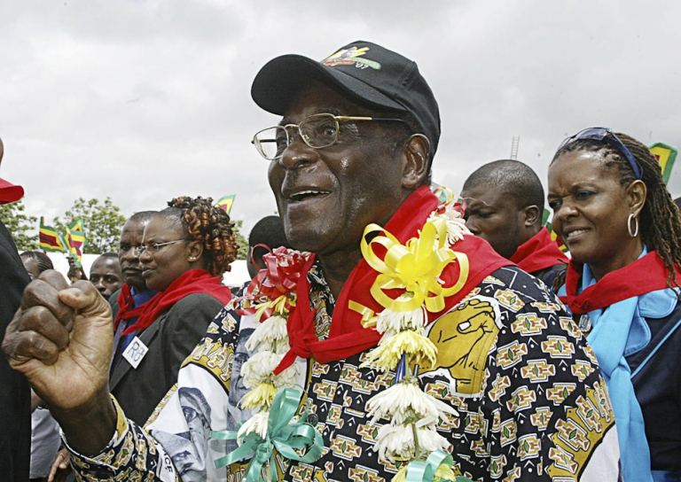 <p>Mugabe goes for a trendy boho layered look on his 83th birthday in 2007, with a patterned shirt, flower lei and red communist-style neckerchief. This was the year that shops in Zimbabwe ran out of bread on Mugabe's birthday.</p>