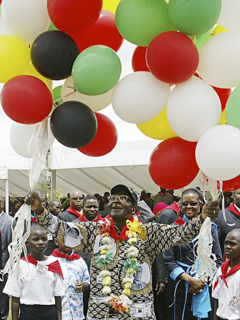 <p>Mugabe's annual birthday tradition of releasing the balloons. And yes, the printed shirt Mugabe is wearing does appear to bear his own image.</p>