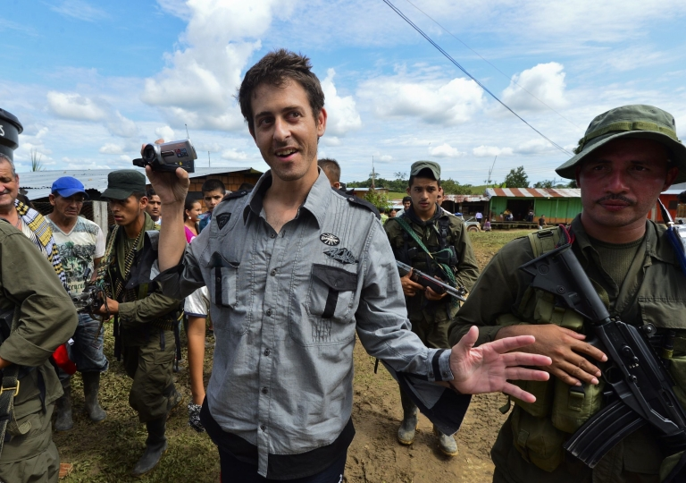 <p>French journalist Romeo Langlois smiles and takes video images as he is taken to be handed over by FARC rebels to a humanitarian mission on May 30, 2012 in the southern department of Caqueta.</p>