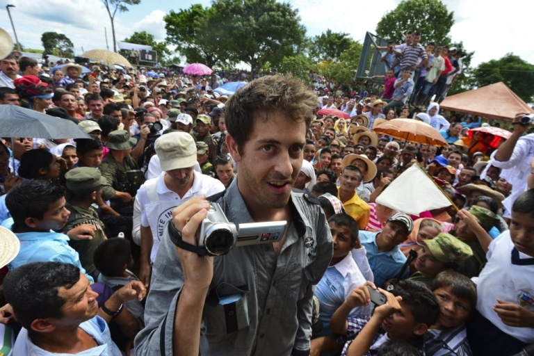 <p>French journalist Romeo Langlois smiles and videos his hand-over from captivity by Colombia's FARC rebel group to a humanitarian commission on May 30, 2012 in the southern department of Caqueta.</p>