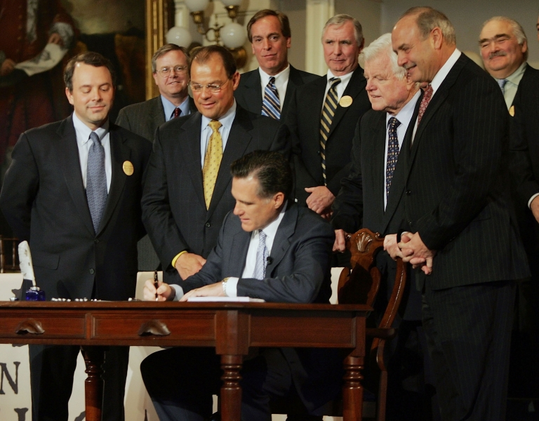 <p>In this archival photo taken on April 12, 2006, Massachusetts Gov. Mitt Romney signs into law a healthcare reform bill that requires all state residents to have health insurance.</p>