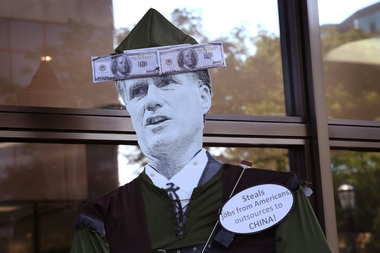 <p>A protester carries a Mitt Romney puppet during a demonstration outside the offices of Bain Capital on Aug. 21, 2012 in Evanston, Illinois. The demonstrators were angry with Bain Capital's plans to move 165 jobs to China from the Sensata Technologies plant in Freeport, Illinois. Bain Capital purchased the Freeport plant two years ago.</p>