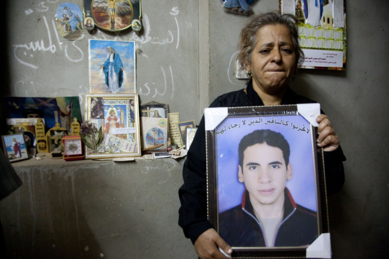 <p>Evon Loga Gabrieul holds a portrait of her deceased son Ayman Nabil Labib, who was beaten to death by classmates on Oct. 16, at her family home in Mellawi, Egypt.</p>