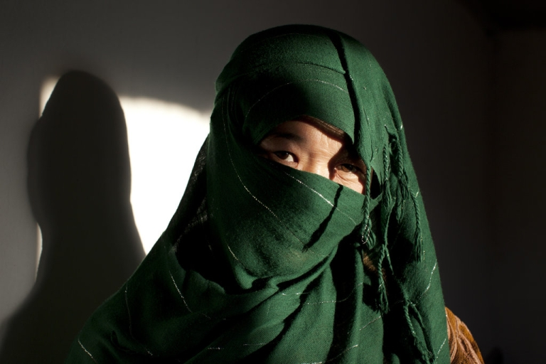 <p>A battered 28-year-old Hazara woman hides behind her veil at a women's shelter October 8, 2010 in Bamiyan, Afghanistan. She came to the shelter after spending five months in prison. She was attempting to divorce her 50-year-old husband.</p>