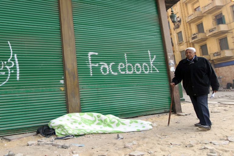 <p>A new Facebook campaign in Egypt has people removing religion from their national identity cards in an innovative anti-sectarian initiative. Here, an Egyptian walks past graffiti at Cairo's Tahrir square on February 7, 2011, during protests that led to the historic overthrow of longtime President Hosni Mubarak.</p>
