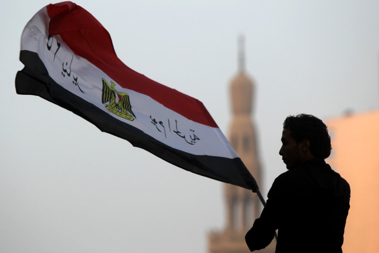 <p>An Egyptian youth waves the national flag with a slogan that reads '25th of January, Day of the Freedom'  following morning prayers in Tahrir Square, the scene of mass demonstration which brought down the regime of former president Hosni Mubarak.</p>