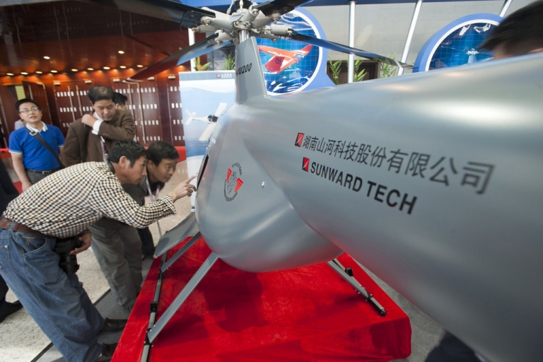 <p>Chinese visitors examining an unmanned helicopter drone from a Chinese manufacturer at the China Aviation Expo in Beijing on September 21, 2011. Beijing on September 22 reacted furiously to a 5.85 billion USD deal to upgrade Taiwan's fleet of F-16 fighter jets, summoning the US ambassador to protest and warning the move would damage relations.</p>