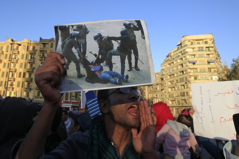 <p>An Egyptian protester holds a modified version of the widely seen image of Egyptian troops beating a veiled woman after having ripped her clothes off to reveal her bra and stomach during recent clashes, at a demonstration against the military rule in Cairo's Tahrir Square on December 22, 2011.</p>