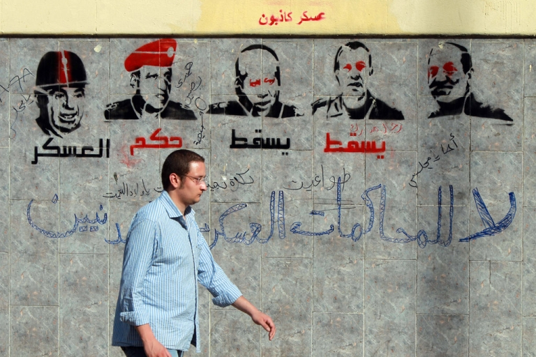 <p>An Egyptian man walks past graffiti depicting members of the military council and reading 'Down with the military rule, no to military trials for civilians' near the defense ministry in the Abbassiya district of Cairo on April 29, 2012.</p>