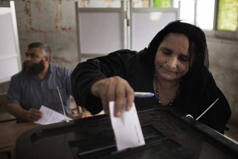 <p>An Egyptian Coptic woman casts her ballot at a polling station in the Manshiyet Nasser district in Cairo on May 23, 2012, during historic presidential elections, the first since a popular uprising toppled Hosni Mubarak.</p>