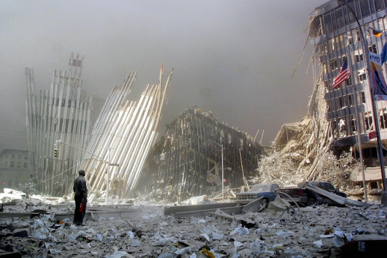 <p>A man stands in the rubble of the north tower of the World Trade Center in New York City, calling out to potential survivors.</p>