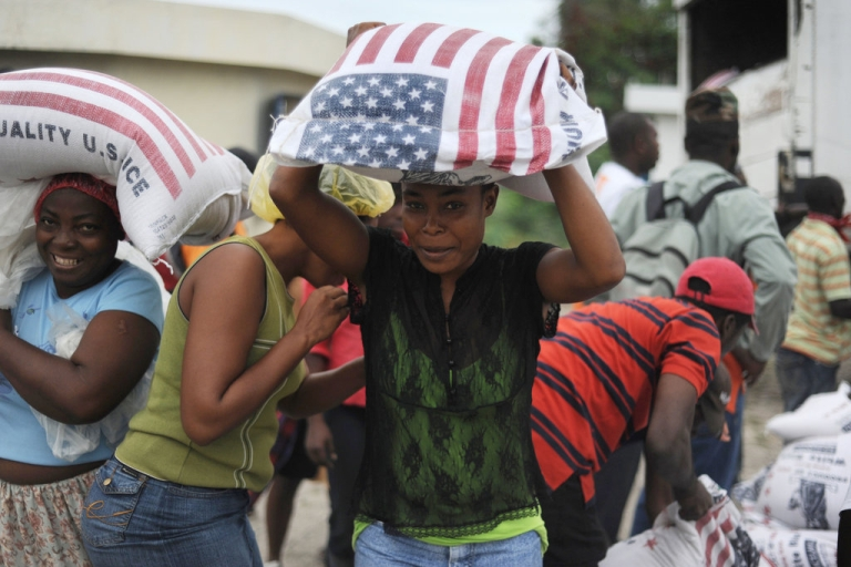 <p>Haitian women get sacks containing rice in Port-au-Prince on March 6, 2010. The World Food Program launched a food 'surge' in Haiti to boost rations for nearly two million people in the impoverished quake-torn country, a spokeswoman said.</p>