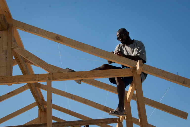<p>A man works to build a church roof using locally purchased, foreign-imported wood in the Neret neighborhood of Port-au-Prince.</p>