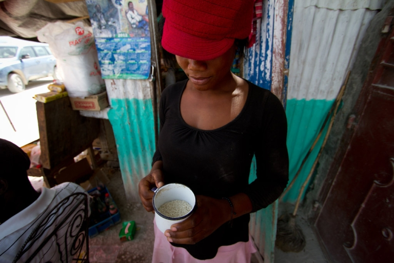 <p>Elene Sainte Somé, 22, sells rice by the cup from her small shop in Coupon, located in Haiti's rice-growing Artibonite region. She says American rice sells better because it's processed to remove rocks and dirt.</p>