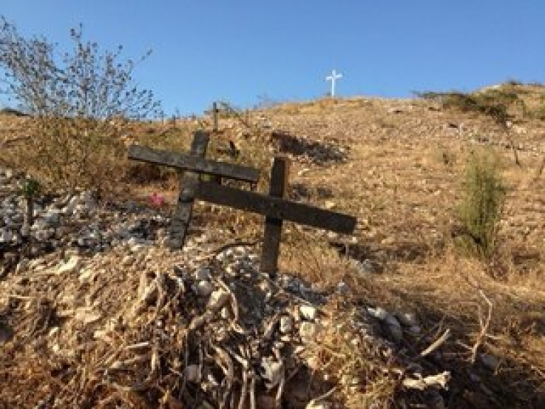 <p>Simple wooden crosses dot a mass grave site in Titanyen, Haiti. As many as 150,000 victims of the 2010 earthquake are buried there.</p>