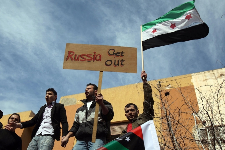 <p>Syrians residing in Libya wave the former Syrian flag as they protest outside the Russian embassy in Tripoli on Feb. 5, 2012. The protest came after Russia and China for the second time vetoed a UN Security Council resolution on the President Bashar al-Assad regime's crackdown on dissent.</p>