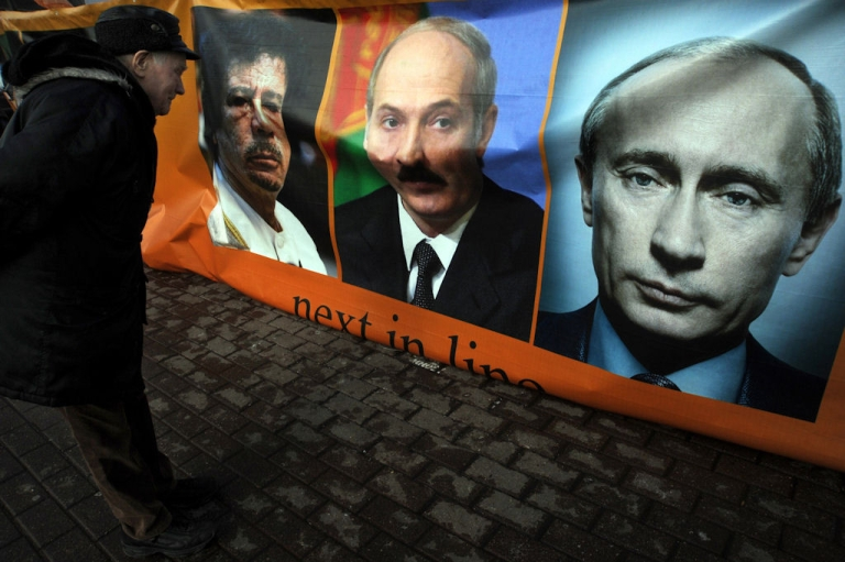<p>A man looks at a banner with portraits of (left to right) Libyan leader Muammar Gaddafi, Belarus President Alexander Lukashenko, Russian Prime Minister Putin and a sign reading