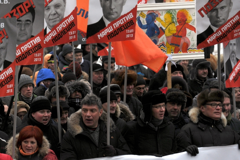 <p>Russian opposition leaders (first row) Boris Nemtsov (2L), Vladimir Ryzhkov (2R) and Mikhail Kasyanov (1R) attend an opposition rally on January 13, 2013, in the center of Moscow against a Kremlin law that bans US adoptions of Russian orphans.</p>
