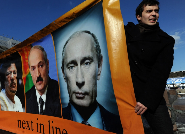<p>Opposition activists hold a banner with portraits of (left to right) Libyan leader Muammar Gaddafi, Belarus President Alexander Lukashenko and Russian Prime Minister Putin during an authorized rally at Pushkinskaya Square in Moscow, on March 13, 2011.</p>