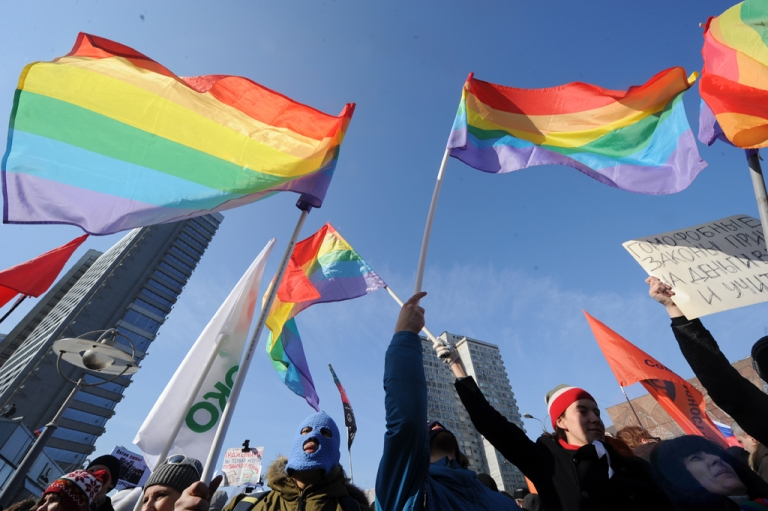 <p>Gay rights activists take part in an anti-Putin rally in the central Arbat area in Moscow, on March 10, 2012. The partly seen makeshift poster (R) criticizes some